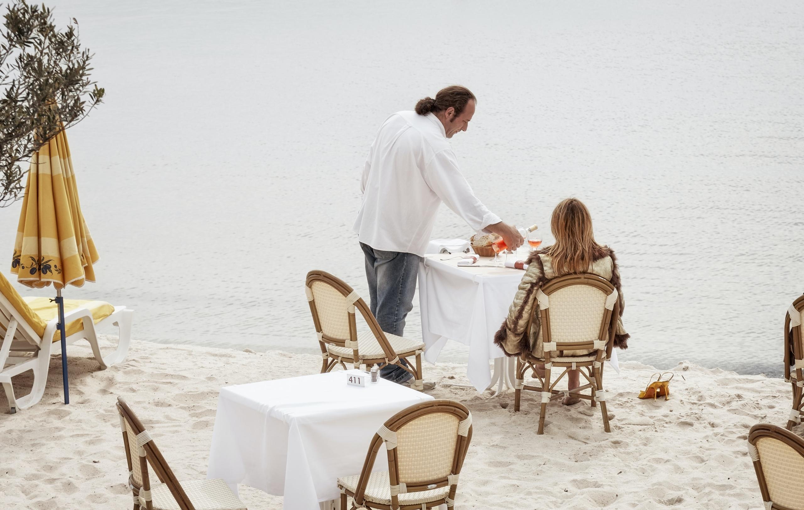 Eine Buchautorin sitzt am Strand und lässt sich vom Kellner bewirten.
